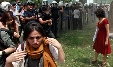 Turkish riot policeman prepares to use tear gas against woman 1