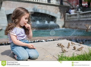 girl-sits-near-fountain-eating-cookies-feeding-birds-jeans-34745031